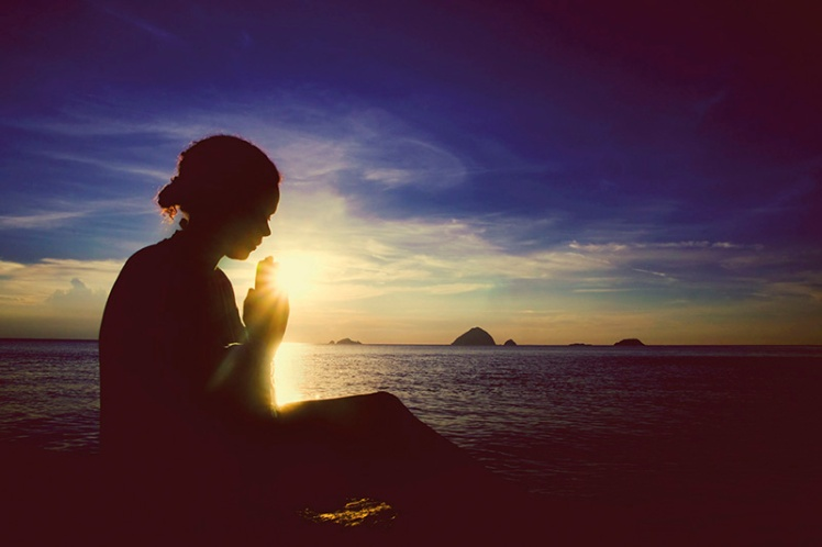 49180882 - young woman praying sunset over the ocean concept
